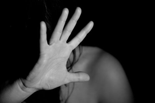 Eine junge Frau hält ihre Hand vor ihr Gesicht, um sich zu schützen.
