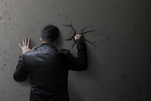 Mann haut gegen eine Wand