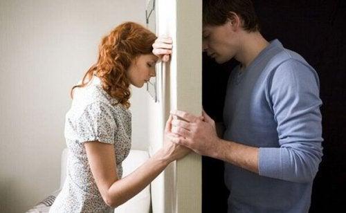 Wütendes Paar auf zwei Seiten einer Wand