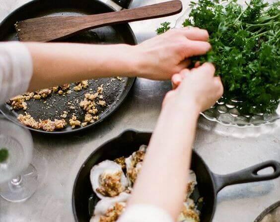 Hände bereiten ein Essen zu und benutzen dazu Kräuter aus einer Schüssel.