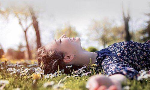 In der Natur auf der grünen Wiese liegende junge Frau