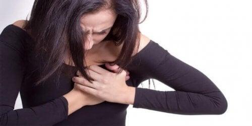 Eine Frau hat Schmerzen in der Brust.