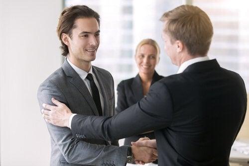 Ein Chef gratuliert seinem Mitarbeiter und klopft ihm auf die Schulter.