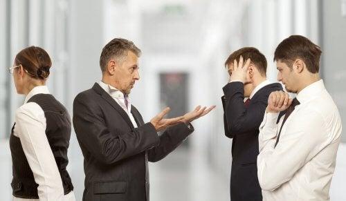 Ein Chef spricht mit zwei seiner Mitarbeiter.