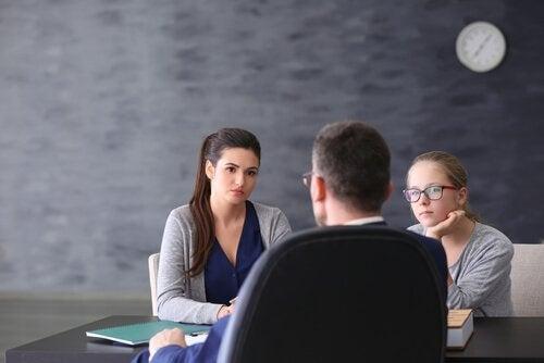Eine Mutter und ihre Tochter sind in einem Gespräch mit dem Lehrer.