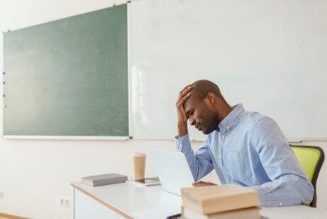 Erschöpfter Lehrer sitzt im Klassenraum.