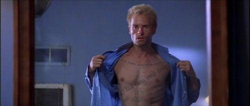 """Filmcharakter aus """"Memento"""", der sein Shirt öffnet und seine Tattoos zeigt."""