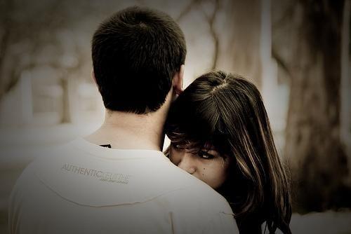 Eine junge Frau lehnt sich an die Schultern ihres Partners an.