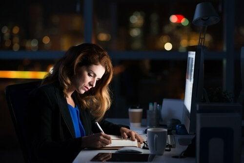 Eine Frau sitzt abends noch im Büro und macht Überstunden.