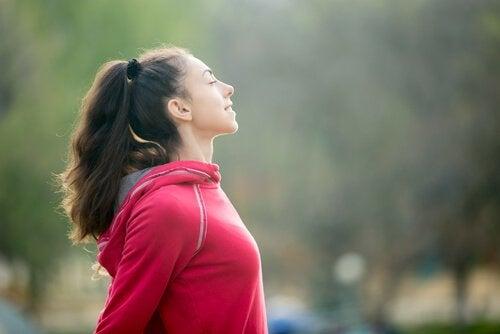 Frau, die nach dem Sport tief einatmet