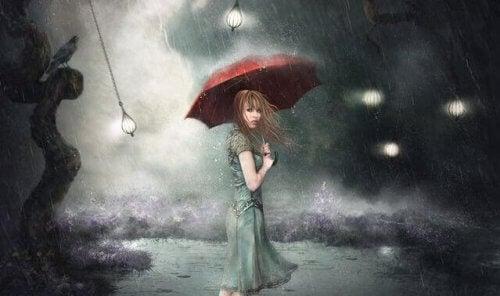 Eine Frau steht mit einem roten Regenschirm im Sturm.