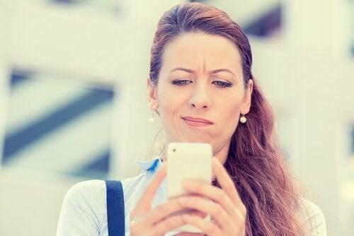 Eine Frau liest skeptisch eine Nachricht.