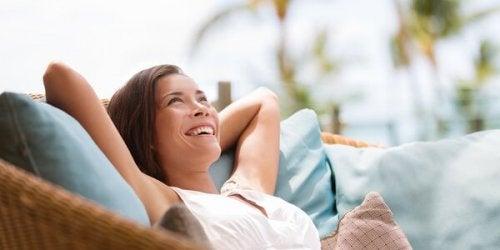 Eine Frau sitzt entspannt in einem Sessel und lacht.