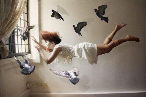 Eine Frau schwebt umgeben von Tauben mitten im Raum.