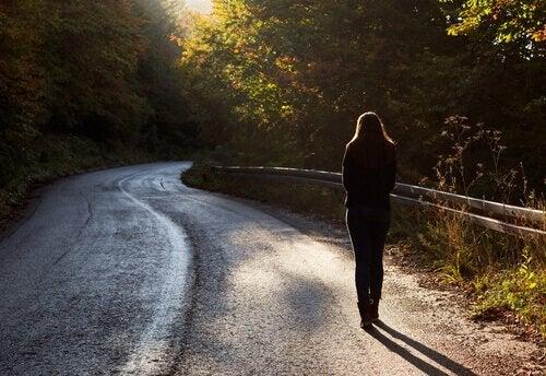 Eine Frau geht durch das Grüne auf einer gewundenen Straße.