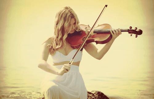 Eine Frau spielt am Meer Geige.