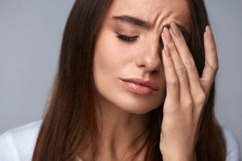 Eine Frau ist gestresst und hält sich eine Hand vor ihr Gesicht.