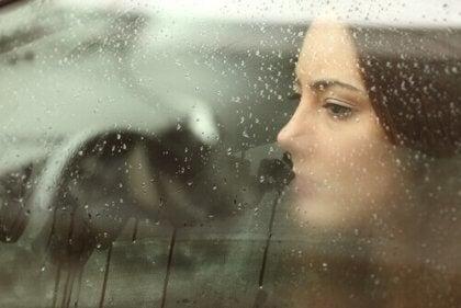 Eine Frau schaut durch ein beschlagenes Fenster.