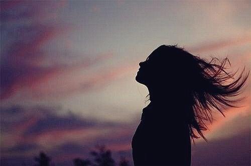 EIne Frau streckt ihren Kopf in Richtung Abendhimmel.