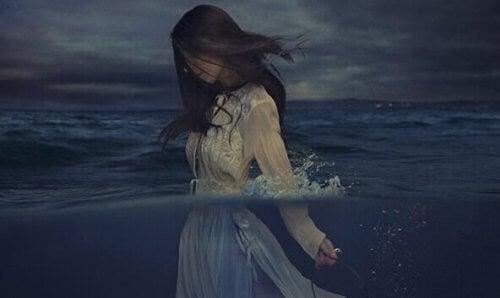 Eine Frau im weißen Kleid steht bis zur Brist im Wasser.