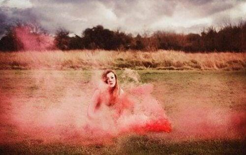 Ein Frau sitzt in rotem Rauch.
