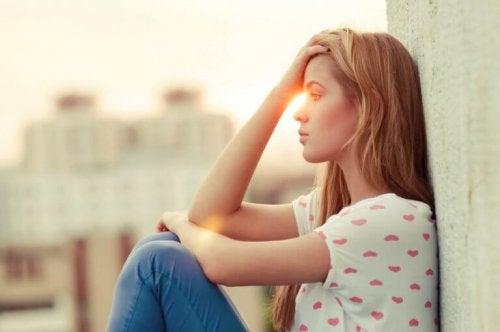 Eine Frau sitzt nachdenklich an einer Mauer, während die Sonne im Hintergrund untergeht.