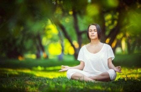 Eine Frau sitzt im Wald und meditiert zur Entspannung.