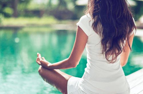 Eine Frau meditiert am Rand eines Pools.