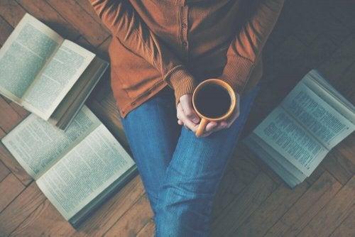 Eine Frau sitzt mit einem Kaffee und um sie liegen ein paar Bücher.