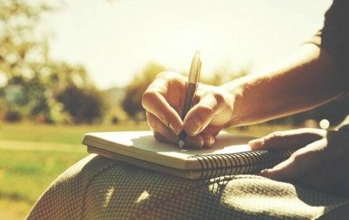Eine Frau schreibt in ihr Notizbuch.