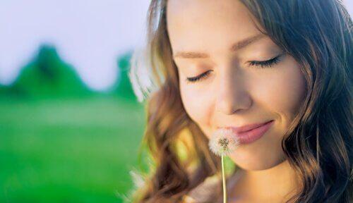 Ein Mädchen lächelt, während sie an einer Pusteblume riecht.
