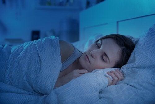 Eine Frau liegt bei gedimmtem Licht im Bett.