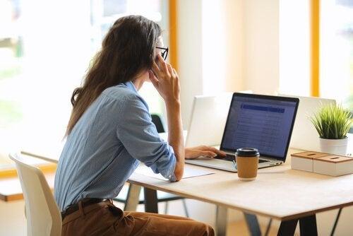 Eine Frau sitzt am Schreibtisch und telefoniert gerade, während sie auf einen Laptopscreen schaut.