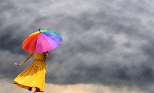 Eine Frau steht mit einem bunten Regenschirm im Regen.
