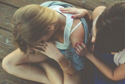 Eine Frau tröstet ihre traurige Freundin.