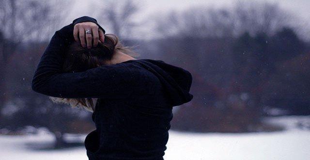 Frustrierte Frau schlägt ihre Arme über dem Kopf zusammen