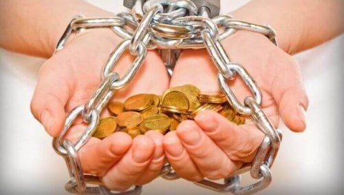 Gefesselte Hände halten eine Menge Münzen.