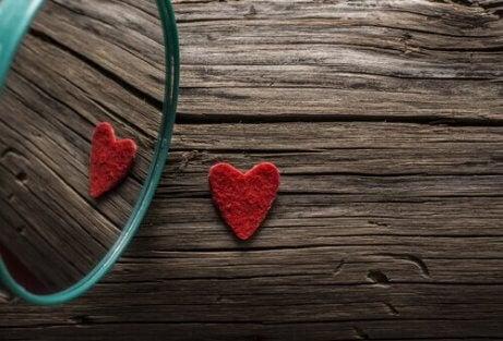 Ein kleines rotes Herz spiegelt sich im Spiegel.