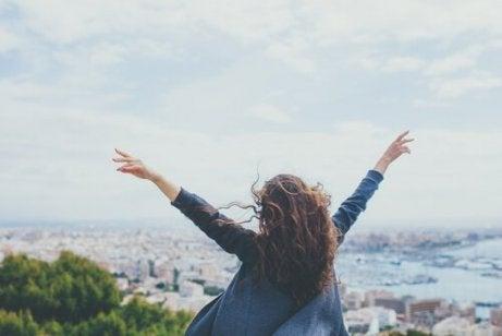 Eine glückliche Frau streckt die Arme gen Himmel.