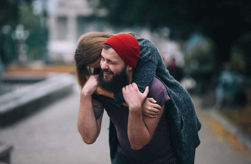Frau umarmt ihren Freund glücklich von hinten