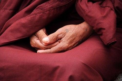 Ein alter Mann hält seine Hände zusammen.