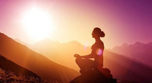 Eine Frau meditiert im Sonnenuntergang vor einer Bergkulisse.
