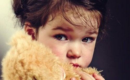 Ein Kind hält einen Teddybären.