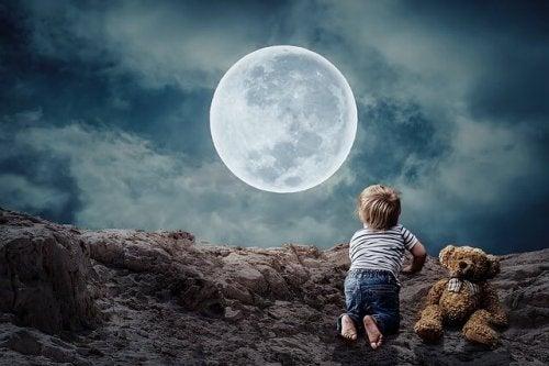 Ein Kleinkind mit Teddy betrachtet den Vollmond.