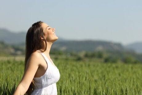 Eine Frau steht auf einem Feld und lächelt.