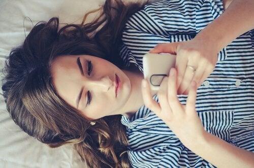 Ein Mädchen liegt auf ihrem Bett, während sie mit ihren Freunden textet.