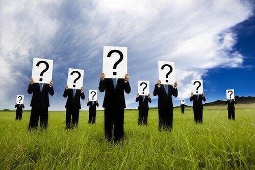 Eine Gruppe von Männern, die auf einer Wiese stehen und Kartons mit Fragezeichen vor ihren Gesichtern halten