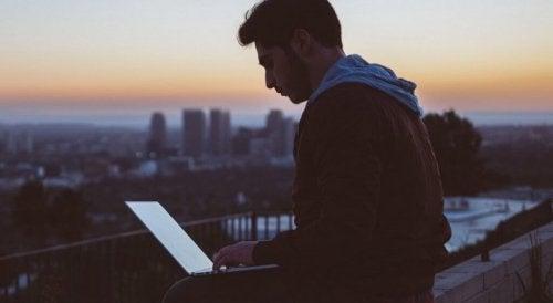 Ein Mann sitzt mit seinem Laptop auf einem Dach.
