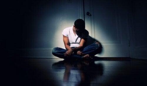 Ein Mann sitzt in einem dunkeln Zimmer.