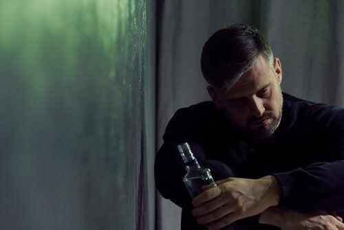Ein verzweifelter Mann hält eine Flasche Alkohol in der Hand.